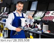 Купить «Confident auto mechanic of car painting workshop pouring paints in paint-spray gun», фото № 28355938, снято 4 апреля 2018 г. (c) Яков Филимонов / Фотобанк Лори