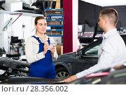 Купить «Woman mechanic with male client», фото № 28356002, снято 4 апреля 2018 г. (c) Яков Филимонов / Фотобанк Лори