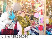 Купить «Happy mother with little daughter buying decorations for Xmas», фото № 28356010, снято 21 сентября 2018 г. (c) Яков Филимонов / Фотобанк Лори