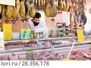 Купить «Male seller offering displayed sorts of meat», фото № 28356178, снято 16 ноября 2016 г. (c) Яков Филимонов / Фотобанк Лори