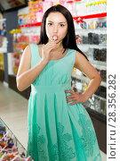 Купить «Woman posing to photographer with lollypop», фото № 28356282, снято 25 апреля 2017 г. (c) Яков Филимонов / Фотобанк Лори