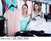 Купить «Customers looking for new garments», фото № 28356354, снято 19 июня 2017 г. (c) Яков Филимонов / Фотобанк Лори