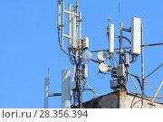 Купить «Антенны базовой станции оператора сотовой связи на крыше здания», фото № 28356394, снято 1 мая 2018 г. (c) Алексей Букреев / Фотобанк Лори