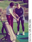 Купить «Golf coach explains the basics of a golfer hitting the ball», фото № 28356586, снято 27 мая 2020 г. (c) Яков Филимонов / Фотобанк Лори