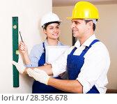 Купить «Constructor showing assistant measuring the wall», фото № 28356678, снято 19 августа 2019 г. (c) Яков Филимонов / Фотобанк Лори