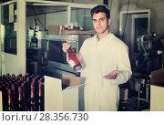 Купить «Man standing in packing section on winemaking factory», фото № 28356730, снято 21 сентября 2016 г. (c) Яков Филимонов / Фотобанк Лори