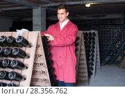Купить «positive man wearing uniform working with bottle storage racks», фото № 28356762, снято 21 сентября 2016 г. (c) Яков Филимонов / Фотобанк Лори