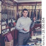 Купить «Salesman showing rifle», фото № 28356854, снято 11 декабря 2017 г. (c) Яков Филимонов / Фотобанк Лори