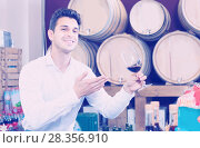 Купить «Happy man customer holding glass of red wine and tasting», фото № 28356910, снято 23 мая 2019 г. (c) Яков Филимонов / Фотобанк Лори
