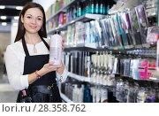 Купить «Positive young female hairstylist in apron showing shampoo», фото № 28358762, снято 31 марта 2018 г. (c) Яков Филимонов / Фотобанк Лори