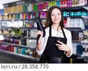 Купить «Female hairdresser in apron holding blow dryer and hair cutters in shop», фото № 28358770, снято 31 марта 2018 г. (c) Яков Филимонов / Фотобанк Лори