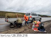 Купить «Ремонт на трассе. Люди ремонтируют автомобильный прицеп на дороге», эксклюзивное фото № 28359218, снято 19 апреля 2018 г. (c) Игорь Низов / Фотобанк Лори