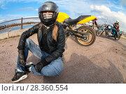 Купить «Девушка байкер сидит на земле рядом с мотоциклом, широкоугольный объектив», фото № 28360554, снято 30 апреля 2018 г. (c) Кекяляйнен Андрей / Фотобанк Лори