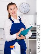 Купить «Cleaner woman 23-26 years old is signing documents while cleaning», фото № 28361362, снято 19 июля 2018 г. (c) Яков Филимонов / Фотобанк Лори