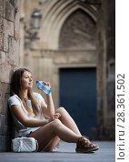 Woman quenching thirst with water sitting near old stone wall. Стоковое фото, фотограф Яков Филимонов / Фотобанк Лори