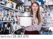 Happy salesgirl showing slow cooker in store. Стоковое фото, фотограф Яков Филимонов / Фотобанк Лори