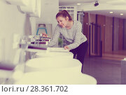 Smiling woman buyer looking ceramic washbasin with tap. Стоковое фото, фотограф Яков Филимонов / Фотобанк Лори
