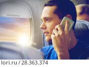 Купить «young man calling on smartphone in plane», фото № 28363374, снято 21 октября 2015 г. (c) Syda Productions / Фотобанк Лори