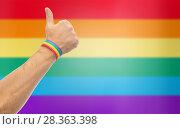 Купить «hand with gay pride rainbow wristband shows thumb», фото № 28363398, снято 2 ноября 2017 г. (c) Syda Productions / Фотобанк Лори