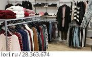 Купить «Ordinary apparel store with different clothes on hangers», видеоролик № 28363674, снято 26 апреля 2018 г. (c) Яков Филимонов / Фотобанк Лори