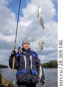 Купить «Рыбак поймал четыре воблы на фидер. Фокус на рыбе», эксклюзивное фото № 28369146, снято 21 апреля 2018 г. (c) Игорь Низов / Фотобанк Лори