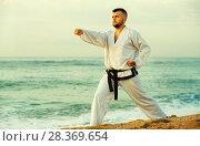 Купить «Guy doing karate poses at sunset sea shore», фото № 28369654, снято 19 июля 2017 г. (c) Яков Филимонов / Фотобанк Лори