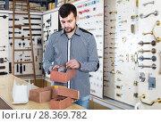 male seller sorting boxes with door handles in houseware shop. Стоковое фото, фотограф Яков Филимонов / Фотобанк Лори