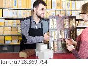 Купить «seller helping female client to choose door hinges in houseware shop», фото № 28369794, снято 5 апреля 2017 г. (c) Яков Филимонов / Фотобанк Лори