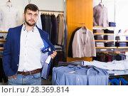 Купить «Happy man customer choosing jacket», фото № 28369814, снято 28 сентября 2017 г. (c) Яков Филимонов / Фотобанк Лори