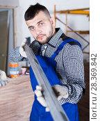 Купить «Professional constructor is looking at the level of the profile», фото № 28369842, снято 3 июня 2017 г. (c) Яков Филимонов / Фотобанк Лори