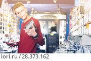 Купить «Male looking CD and DVD in shop attentively reading contents», фото № 28373162, снято 15 февраля 2018 г. (c) Яков Филимонов / Фотобанк Лори