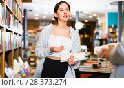 Attractive Brazilian girl discussing books with other visitor of bookstore. Стоковое фото, фотограф Яков Филимонов / Фотобанк Лори