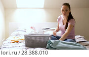 Купить «woman or housewife sorting laundry at home», видеоролик № 28388010, снято 30 апреля 2018 г. (c) Syda Productions / Фотобанк Лори
