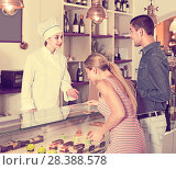 Купить «Positive pastry chef female is offering cakes from showcase», фото № 28388578, снято 5 июня 2017 г. (c) Яков Филимонов / Фотобанк Лори