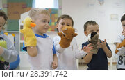 Купить «Children's developing a game room. Emotions of young children during entertaining classes. Kids will have fun playing with dolls that are put on the hand.», видеоролик № 28391742, снято 6 декабря 2019 г. (c) Константин Мерцалов / Фотобанк Лори