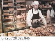 Купить «Smiling male pastry maker demonstrating croissant», фото № 28393846, снято 26 января 2017 г. (c) Яков Филимонов / Фотобанк Лори