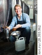 Купить «man pouring wine from wood in cellar», фото № 28393962, снято 23 июля 2018 г. (c) Яков Филимонов / Фотобанк Лори