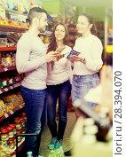 Купить «People discussing something in shop», фото № 28394070, снято 25 июня 2018 г. (c) Яков Филимонов / Фотобанк Лори