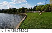 Купить «Moscow, Russia - May 07. 2018. people are resting on shores of the city pond in Zelenograd», видеоролик № 28394502, снято 9 мая 2018 г. (c) Володина Ольга / Фотобанк Лори