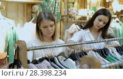 Купить «Portrait of smiling women choosing clothes in the modern shop», видеоролик № 28398234, снято 27 марта 2018 г. (c) Яков Филимонов / Фотобанк Лори