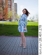 Купить «The beautiful girl in a blue short dress costs against the background of the street per windy sunny day», фото № 28401278, снято 1 мая 2018 г. (c) Anatoly Timofeev / Фотобанк Лори