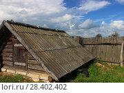 Купить «Деревенский пейзаж – шиферная крыша старого амбара и деревянный покосившийся серый забор на фоне ярко-голубого неба с облаками», фото № 28402402, снято 12 июля 2015 г. (c) Илья Илмарин / Фотобанк Лори