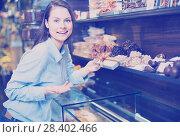 Купить «Smiling girl choosing delicious ganaches, praline», фото № 28402466, снято 31 марта 2020 г. (c) Яков Филимонов / Фотобанк Лори
