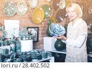 Купить «Mature woman posing with ceramic cookware», фото № 28402502, снято 31 октября 2016 г. (c) Яков Филимонов / Фотобанк Лори