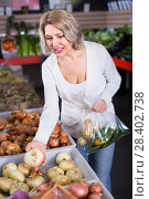 Купить «Woman selecting veggies in grocery», фото № 28402738, снято 26 мая 2019 г. (c) Яков Филимонов / Фотобанк Лори