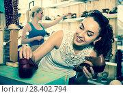 Купить «Young woman choosing a pair of shoes», фото № 28402794, снято 20 июля 2018 г. (c) Яков Филимонов / Фотобанк Лори