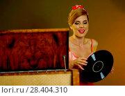 Купить «Retro woman with music vinyl record. Girl pin-up style wearing red dress.», фото № 28404310, снято 21 сентября 2018 г. (c) Gennadiy Poznyakov / Фотобанк Лори