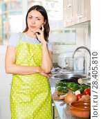 Купить «Sad young girl housewife in apron at home kitchen», фото № 28405810, снято 18 апреля 2018 г. (c) Яков Филимонов / Фотобанк Лори