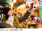 Купить «Young girl choosing Christmas decoration», фото № 28406170, снято 12 декабря 2016 г. (c) Яков Филимонов / Фотобанк Лори
