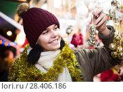 Купить «girl choosing Christmas decoration at market», фото № 28406186, снято 12 декабря 2016 г. (c) Яков Филимонов / Фотобанк Лори